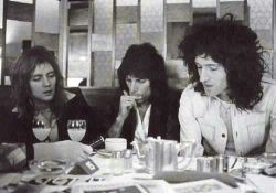 Roger Taylor, Freddie Mercury, and Brian May at dinner.