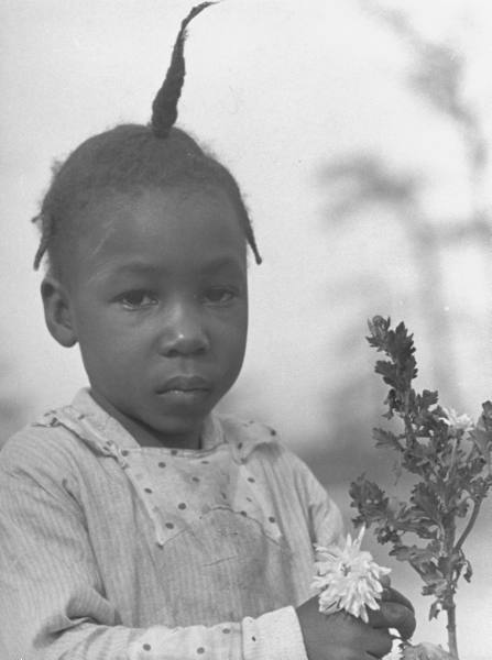 alfred eisenstaedt - young sharecropper's daughter posing wistfully with a flowering plant on a farm, greenville, ms, 1937