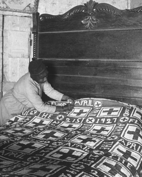 alfred eisenstaedt - sharecropper's wife lizzie alexander mending the red cross quilt she made commemorating the regional flood of 1927, ms, 1937