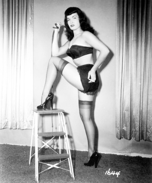 Bettie Page holding a cigarette though she never smoked or drank. She would sometimes hold one in the Irving Klaw shots.