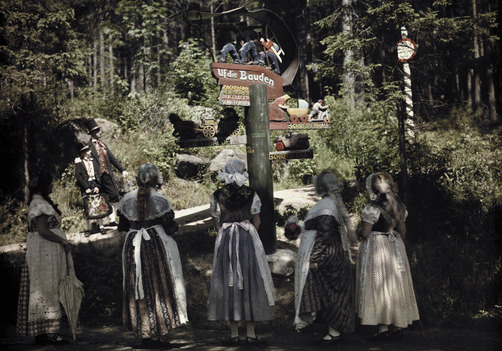 Young girls in bonnets and aprons stand reading a signpost. Location:Schreiberhau, Lower Sisela, Germany.Photographer:WILHELM TOBIEN/National Geographic Stock