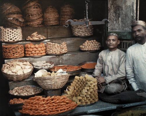 Two merchants sit by their stand of honeycakes in bombay. Location:Bombay (Mumbay), India.Photographer:GERVAIS COURTELLEMONT/National Geographic Stock