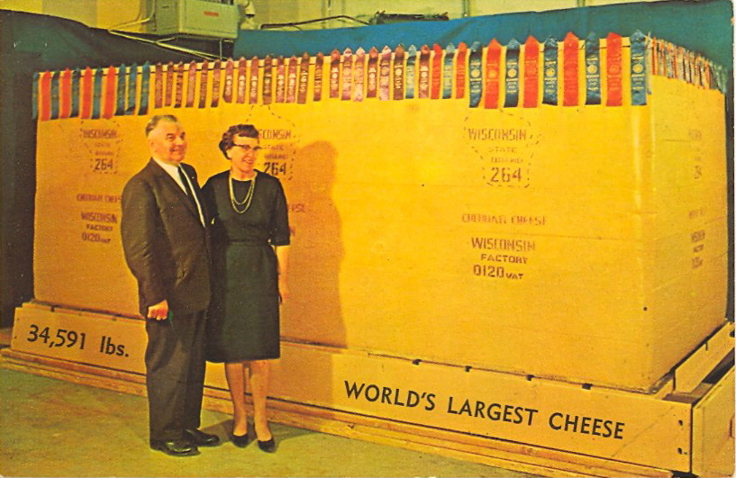 STEVE'S CHEESE—WORLD'S LARGEST! 34,591 pounds!  MADE BY STEVE'S CHEESEDENMARK, WISCONSIN This famous cheese is on display at the New York World's Fair. We mail and express Gift Boxes. Our Specialty is Natural Wisconsin Cheddar; Mild, Aged and Old.   Wonder if that's Steve with his wife?