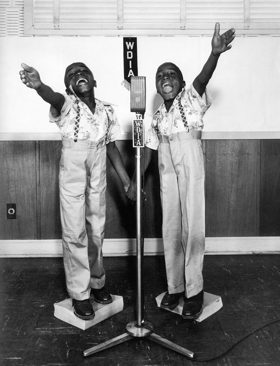 "© Ernest Withers. Twins at WDIA, 1948. Gelatin silver print. Panopticon Gallery's newest exhibition, Kids Are People Too, celebrates children in photography as explored through the vision of sixteen photographers, from the well known to the emerging contemporary artist. Inspired by Jason Landry's own memories of youth, the gallery owner and curator, says, ""When I was a boy there was a TV show called, Kids Are People Too. It was like a talk show for kids: a Sunday morning variety show.  My fondest memory of that show was the time that they had my favorite rock band on, KISS. Isn't it interesting that some childhood memories are quite vivid, while others are long forgotten?"" The exhibition is on view from June 8, 2011 until July 12, 2011."