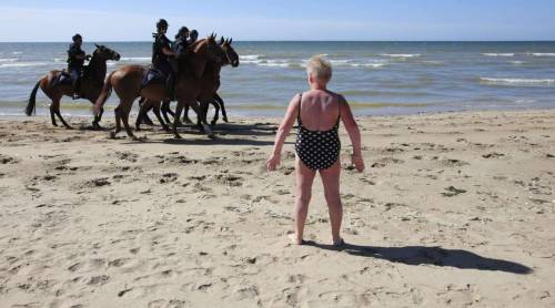 csmphoto:     A bather watches as French police on horses patrol the beach near the venue of the G8 summit in Deauville, northern France, May 25, 2011. Police today sealed off the area around the venue where the leaders of the G8 countries are due to meet in Deauville on May 26-7. REUTERS/Andrew Winning  I love it when news and features meet in the middle. This is the perfect example.  Check out more of my choices for Photos of the day for 5/25/11.       Ann Hermes/Staff Photographer