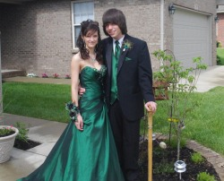 "Well, my senior Prom is officially over. It  was actually two weekends ago, on the 14th.. But I just now remembered  that I wanted to submit a photo to you guys! This is me and my boyfriend  at his house right before we went out to eat with everyone. As you can tell, our theme was peacock feathers. I have six on my  Precious Formals dress, three in my corsage, two in my hair, and one on  my clutch. He has one as a boutonniere. I think we looked rather nice. *He also had a cane with a wolf head carved on the top and ""Nothing But A G Thing"" engraved down the side. Needless to say, Senior Prom was definitely a success! Enjoy, dears! —————————————————— Submitted by saraneedsair LOVE the peacock theme!  So original, yet such a ridiculously wonderful idea that we can't believe this isn't commonplace for prom yet."