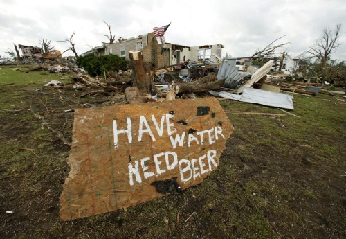 "A sign read ""Have water, need beer"" in tornado-ravaged Joplin, Missouri,  Wednesday. The death toll climbed to 125 from Sunday's tornado there.  Meanwhile, at least 14 people were killed in Arkansas, Kansas and  Oklahoma in new storms Tuesday night. (Photo: Charlie Riedel / AP via the Wall St. Journal)"