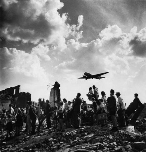 Berlin, GermanyJune 1948  Citizens of Berlin stand amid rubble near the edge of Tempelhof Airfield to watch an American C-47 cargo plane arrive w. food & supplies, part of the Allied effort to counter a Soviet blockade of the city during the Berlin airlift.  Photograph by Walter Sanders/LIFE Magazine