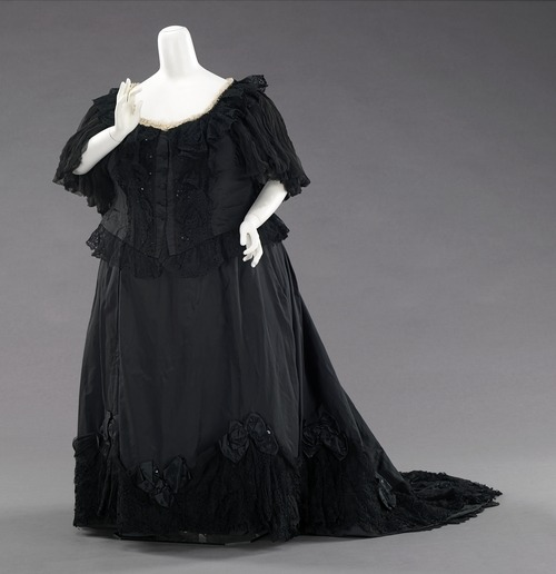 c. 1894-95 The Met says: This gown was once worn by Queen Victoria (1819-1901) of the United Kingdom. Purchased from an annual sale of the Queen's garments, it shows the traditional touches of mourning attire, which she wore from the death of her husband, Prince Albert (1819-1861), until her own death. The gown follows the style of the period and is finely detailed inside and out, details which would be expected by a Queen. Black mourning dress reached its peak during Queen Victoria's reign. She set the standard by wearing mourning for half of her life. With these standards in place, it was considered a social requisite to don black from anywhere between three months to two and a half years while grieving for a loved one or monarch. The stringent social custom existed for all classes and was available at all price points. Those who could not afford the change of dress often altered and dyed their regular garments black. The amount of black to be worn was dictated by several different phases of mourning; full mourning ensembles were solid black while half mourning allowed the wearer to add a small amount of white or purple.