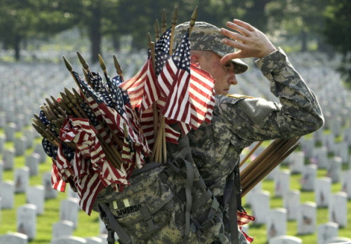 Army Spc. Justin Immerso places flags in front of head stones at Arlington National Cemetery in preparation for Memorial Day, in Arlington, Va. Photo Credit: Jacquelyn Martin/AP via the Globe and Mail