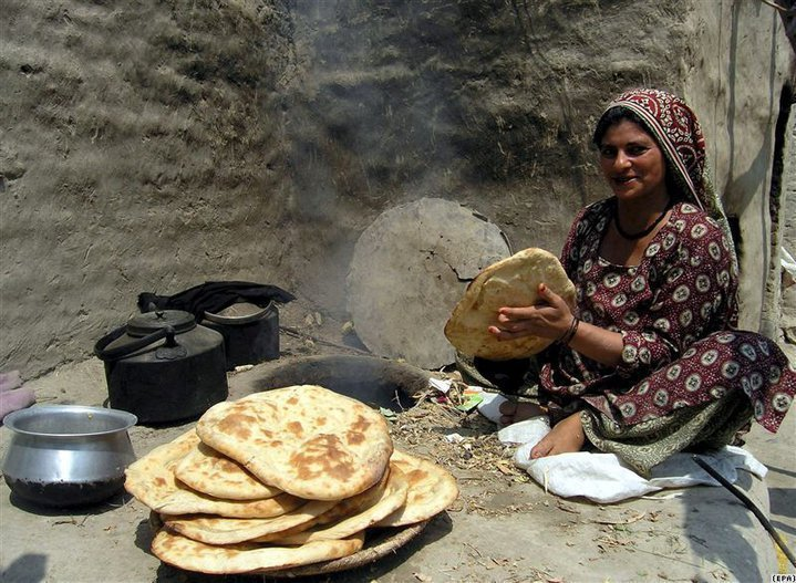 "Afghan woman, baking bread (naan), in a ground tandoor (tanoor). Every family (if can afford it) have maximum 2 tandoors in their house. One inside the house in a separate room known as "" woorjai"" or a fireplace, and one out side the house in an outdoor kitchen. That is because in summer they bake bread outside the house and in winters inside.     Tandoor have other purposes as well, the reason bread is baked inside the house in winters, because when they light fire in a tandoor a system is made under the house, such that the heat from the fire is distributed to the nearby rooms keeping them warm in winter. After the baking is over the hot tandoor is used to keep water pots in to boil for later use, which is then used for many purposes making tea, or hot water for shower etc."