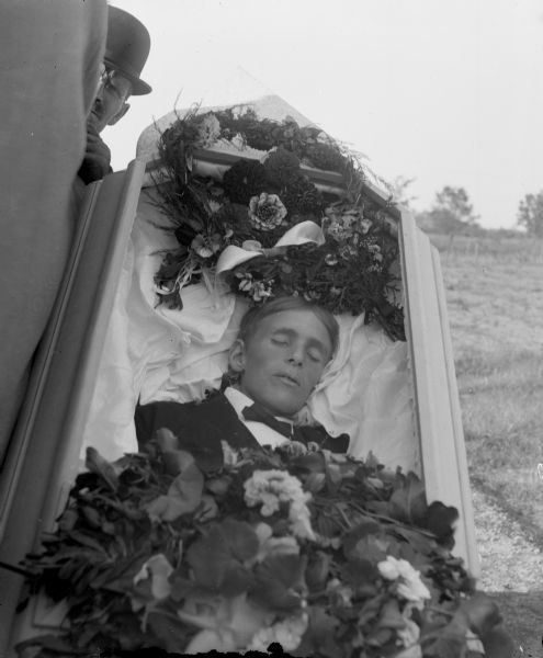 "Charles Van Schaick, ""Open Casket with Body of European American Man,"" undated. Black River Falls, Wisconsin. Source: Wisconsin Historical Society. Photoarchivist's desciption:   Open casket with the corpse of an European American man lying inside it wearing a dark-colored suit coat and bow tie. Floral arrangements are placed above his head and on top of his midsection. Another man wearing a derby is visible looking from behind the casket.  I would never have noticed the derby-hatted man if this hadn't been in the description, and this picture is about twice as amazing now that I've noticed it.  That said, I think I should take a moment to express how thankful I am for the archivists at the Wisconsin Historical Society. Their online collections are really fabulous, and I owe a lot to them for many of my favorite posts on my other Tumblr blogs."
