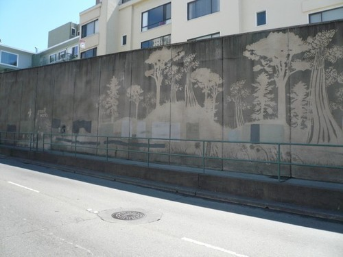 dancingonembers:   reverse graffiti. instead of using actual spray cans…some artist are just cleaning dirt off of certain areas to make their masterpieces. and they are calling it reverse graffiti. kind of brilliant.   [wall by a road, with reverse graffiti in the shape of tree-shapes on rolling hills]