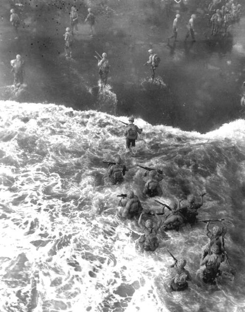 December  26, 1943: U.S. Marines are seen from above as they wade through rough  water to take the beach at Cape Gloucester on New Britain, Papua New  Guinea. (AP Photo)