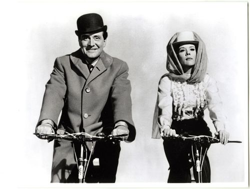 Patrick Macnee and Diana Rigg ride bikes.