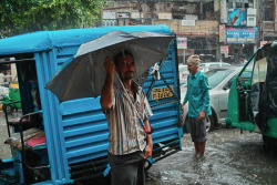 INDIA. Delhi. Man with umbrella. ⓒ Julie Mayfeng