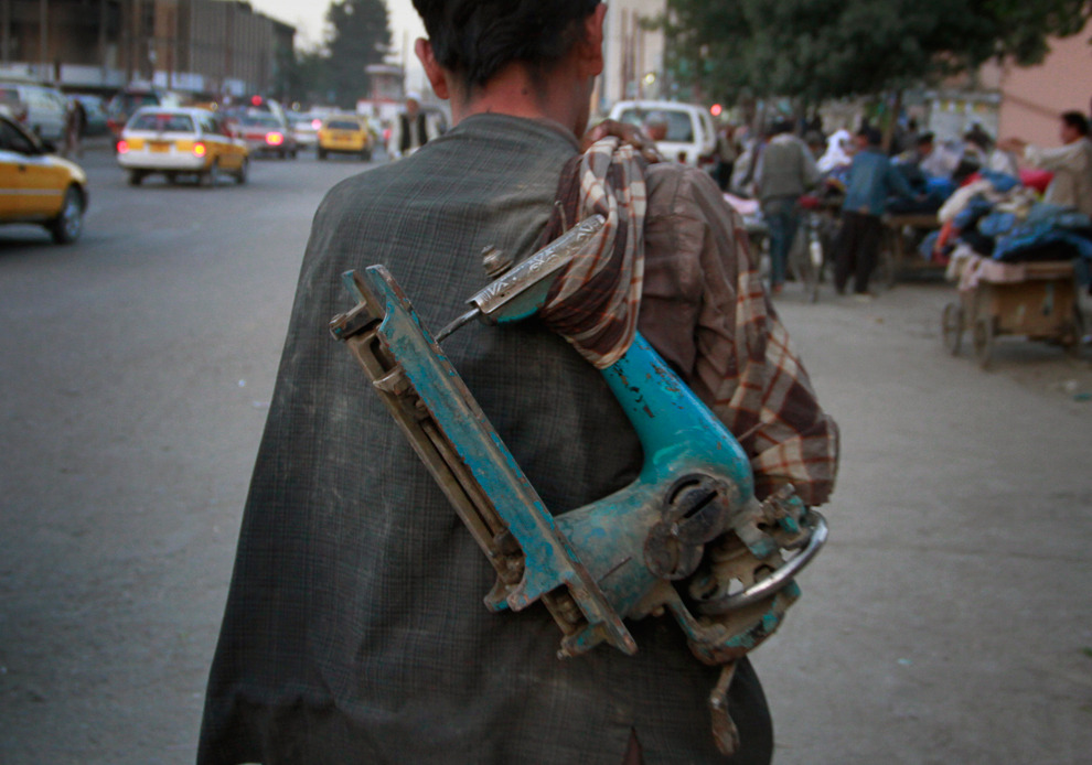 An Afghan man carries a broken and old sewing machine to sell in Kabul, Afghanistan May 16, 2011 via