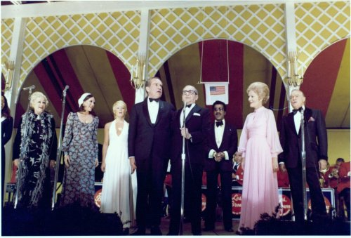 "Irving Berlin and other stars at the White House Richard Nixon is joined by First Lady Pat Nixon and several celebrities in the singing of ""God Bless America."" (Left to Right) Phyllis Diller, Mary Ann Mobley, Joey Heatherton, President Nixon, Irving Berlin, Sammy Davis Jr., Pat Nixon, and Bob Hope.  The event was a White House Dinner for POW's held on May 24, 1973."