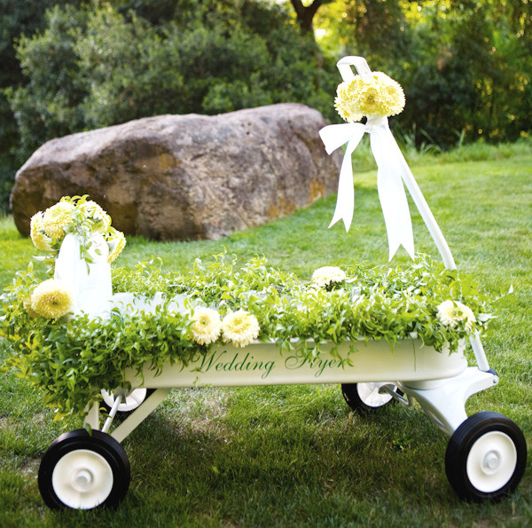 """The aisle was decorated with hanging baskets of white hydrangeas. The young flower girl came down the aisle in a special """"Wedding Flyer"""" wagon. (via Snippet & Ink)"""
