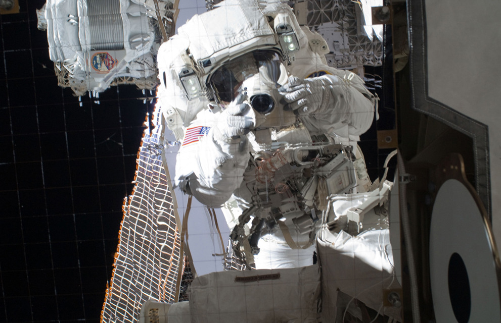 Astronaut Michael Fincke takes a photo of his reflection on the outside of the International Space Station during a spacewalk. Astronaut Takes Photo of Reflection while on a Spacewalk