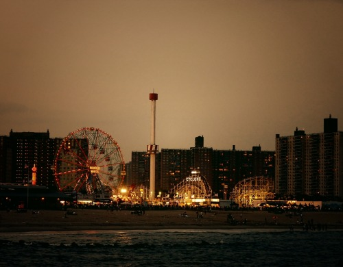 "nythroughthelens:  The beach at Coney Island. Brooklyn, New York City. There is nothing quite like the view of the Wonder Wheel and the Cyclone roller coaster all lit up with the ocean and the beach in the foreground. Nothing. ""Between about 1880 and World War II, Coney Island was the largest amusement area in the United States, attracting several million visitors per year. At its height it contained three competing major amusement parks, Luna Park, Dreamland, and Steeplechase Park, as well as many independent amusements. Astroland served as a major amusement park from 1962 to 2008, and was replaced by a new incarnation of Dreamland in 2009 and of Luna Park in 2010. The other parks and attractions include Deno's Wonder Wheel Amusement Park, 12th Street Amusements, and Kiddie Park, while the Eldorado Arcade has an indoor bumper car ride. On April 20, 2011, the first new roller coasters to be built at Coney Island in eighty years were opened as part of efforts to reverse the decline of the amusement area. Wonder Wheel – built in 1918 and opened in 1920, this steel Ferris wheel has both stationary cars and rocking cars that slide along a track. It holds 144 riders, stands 150 ft (46 m) tall, and weighs over 2,000 tons. At night the Wonder Wheel's steel frame is outlined and illuminated by neon tubes. It is located at Deno's Wonder Wheel Amusement Park. The Cyclone roller coaster – built in 1927, it is one of America's oldest wooden coasters still in operation. Popular with roller coaster aficionados, the Cyclone includes an 85 ft (26 m), sixty degree drop. It is owned by the City of New York, and was operated by Astroland, under a franchise agreement. It is located across the street from Astroland."" - Source —- Coney Island at Night Posters and Prints are available for purchase by clicking here"