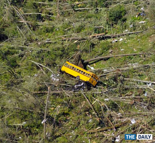thedailyfeed:  A school bus lies amid downed trees at the Village Green Family Campground in Brimfield, 30 miles east of Springfield. —MASS. DESTRUCTION, The Daily  Wow. What a striking, disturbing image. We really, really hope that school bus was empty.