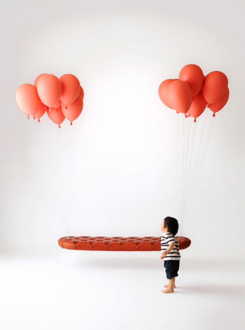 """The Balloon Bench"" [by Satoshi Itasaka] appears to be suspended in mid air, held up by two bunches of red balloons, yet the reality is Itasaka suspended his creation from the ceiling by 4 anchors concealed by the shapes of the balloon bundles.  ""Smoke and mirrors"" is the famous saying among movie makers… things are not always what they seem.   Itasaka successfully creates the illusion that a substantial bench is lifted by only a few delicate balloons."
