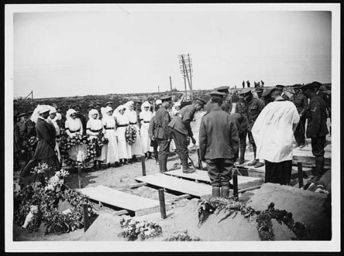 Lowering the coffin by National Library of Scotland on Flickr:  Funeral of a Red Cross nurse, Western Front, during World War I. Soldiers lowering the coffin of a Red Cross nurse into a grave. Other nurses stand around holding wreaths and a bugler is waiting at the head of the grave. This is one of three photographs of the funeral which are attributed to Tom Aitken. In spite of the huge numbers of men killed during the war, these photographs suggest that there was still an element of shock at the death of a woman, especially a nurse.