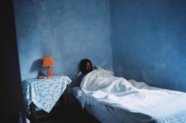 by Adeline Mai, blue bedroom, orange lamp, asian girl.
