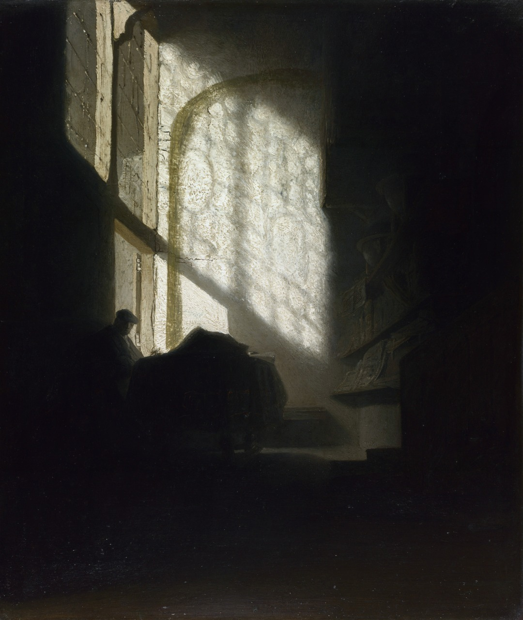 A Man seated reading at a Table in a Lofty Room, unknown follower of Rembrandt, circa 1630.