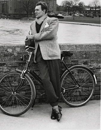 Michael Redgrave stands by a bike.