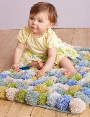 Pom Pom Rug | Lion Brand Yarn OK, quickly: how cute is that baby?! Now that's out of the way, how cute is this rug?! This is one of my favourite posts in a long time. Pom poms are so easy to make, and trust me, this would feel so nice underfoot! Plus, you can customise it to fit in with your decor. Get started on your pom poms folks!