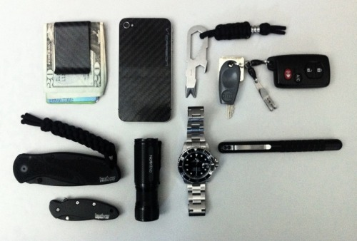 submitted by Matt  Big fan of the site.  Here's my carry going clockwise: -Koolstof Carbon Fiber Money Clip-iPhone 4 with carbon fiber backing-Atwood G5 Prybaby with TI Lanslide-Keys with P-7 Suspension Clip and fishing swivels-County Comm Embassy Pen-Rolex Submariner-Novatac Storm-Kershaw Chive-Kershaw Blur  Editor's Note: Nice loadout, things are pretty streamlined here. The moneyclip and iPhone protection are a good look, keeping those front pockets nice and slim it looks like. I also like seeing the P7 suspension clip on your rather minimalist keys — it's difficult to deal with those RFID fobs, especially with your car remote tacked on there too. Novatac, Atwood, Sub and Embassy Pen are pretty much bombproof, so good choices with that. I see a bit of redundancy in your main blade and backup blade which makes me wonder a little… There's the option of picking a backup blade that emulates your main blade's function, or you could get a different backup to complement your primary (like a different blade shape, locking mechanism, etc). In any case, nice loadout and thanks for sharing.