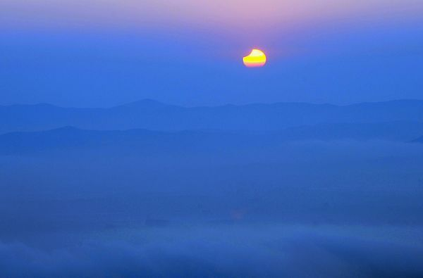 The partially eclipsed sun swings low over misty mountains in Changchun, China, early this morning. The first hint of the moon's silhouette taking a bite out of the sun's disk was seen from northern China and northern Japan between 4 and 5 a.m., local time, on Thursday. Shortly thereafter, about 60 percent of the sun went dark over Siberia, Russia. Moving east to west, the solar eclipse's pathway crossed the date line, so far-northern European observers saw the eclipse around 11:30 p.m., local time, on Wednesday.