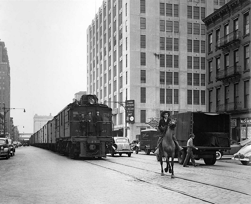 "Train on street level in New York, 1934.  Freight traffic in the area began on street level in 1847, delivering dairy, meat and produce to factories and packing plants on the West Side near the Hudson River. The trains crashed so often with traffic — first carriages, then cars — that 10th Avenue was dubbed ""Death Avenue."" Signalmen on horses waving red flags dubbed West Side Cowboys weren't much help, so the tracks were elevated in 1934. (Friends of the High Line via AP)"