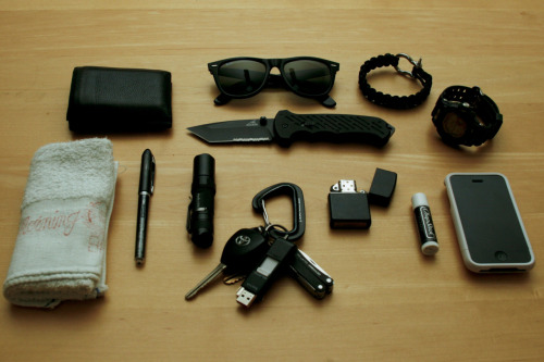 submitted by jer-d  My everyday carry, for a college student in California. Many items were inspired by following this blog, especially my Fenix LD10. Going for a murdered out theme (except my iPhone) iPhone 3GS w/ White Incase SliderChapstickZippo Black Matte LighterCasio G Shock GW9200-1 Solar Atomic WatchBlack 550 Paracord BraceletOriginal Rayban Wayfarers (Black)Gerber 06 Fast Tanto BladeFenix LD10Uni-Ball Vision Elite W PenBlack Leather WalletSmall White Hand TowelKeys: Metolius Carabiner, SanDisk 4GB Flash Drive, Leatherman Squirt ES4 Multitool  Editor's Note: Cool, I'm a college student in CA too~ I can see you want all of your bases covered, going so far as to keep cordage, a source of fire and even a towel with you! That's more than I'd carry on my person but I do keep those things in my bag (a small hand towel comes in handy more than I thought it would, at least in the summer it did). Anyway, I like that beefy carabiner for key retention, I'd just advise to have your car key detachable so as to avoid any ignition strain just in case… Some last observations — your wallet looks a little on the thicker side, you may want to consider it time to clear out unnecessary cards, receipts, etc or find a slimmer wallet especially if you back pocket carry. Carrying anything in your back pockets and sitting on it could lead to back problems in the long run. Oh, and the knife with the combo edge and tanto point in all black might be a bit aggressive-looking for campus carry, maybe look into another knife to add to your rotation. Overall it looks like a sturdy and versatile carry, so keep that up. Thanks for sharing!