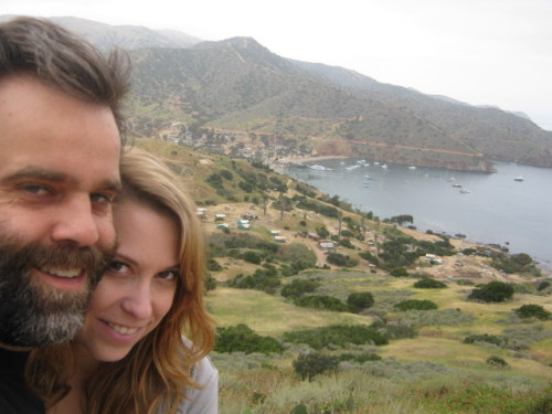 "This is us on Catalina Island, a couple of months before our Chilean adventure begins.  Right now we are getting ready to go. Selling stuff, giving stuff away, visiting friends and family, packing, getting visas (complicated and boring), seeing as much of L.A. as we can, and generally loving the process. We have a bucket list that mostly includes food. We must go to Nichol's in the Marina for the best egg sandwich ever made, Ronnie's Dinner on Culver for a Chorizo Bowl, Cactus on Vine for the best tacos in L.A., Father's Office in Culver City for a burger, and The Griddle on Sunset for some giant pancakes! Also we'd like to get back to The Upright Citizens Brigade before we take off. I quit my job about a week ago and have become half house-girlfriend-half personal secretary to Tom. It's been nice and actually much busier than I thought it would be. As it turns out talking to the Chilean Consulate and the Department of Justice and Kaiser and trying to coordinate all of the things we need for a visa is a full time job.  Believe it or not, talking to the government is not enjoyable. Especially when you are on a super tight timeline and your future pretty much depends on their cooperation. It hasn't been all work though; we go swimming every morning (which is a fantastic way to start the day) and today we had a nice long lunch. Last Friday I got to go to work with Tom because his company was having a lunchtime BBQ to celebrate our going away to Chile and to just generally say goodbye for a bit since everyone in the company seems to be going out of town/the country for awhile at the same time. I like bring your girlfriend to work day, more companies should encourage that :) I'm pretty excited that my worldly possessions have been narrowed down from what fit into a large moving truck a year ago to about four boxes and about a quarter of the wardrobe I had a year ago. It's a pretty freeing feeling. As Tom would say I'm ""foot loose and fancy free"", which basically just means I can go wherever I want now without having to haul around a bunch of meaningless crap. Like I said, it's a nice feeling!   Well that's it for now, first post is done, lots more to come, probably mostly involving food :)"