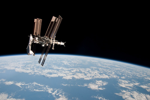 Space Station Over Earth by NASA's Marshall Space Flight Center on Flickr. The pictures are the first taken of a shuttle docked to the International Space Station from the perspective of a Russian Soyuz spacecraft. Image credit: NASA.