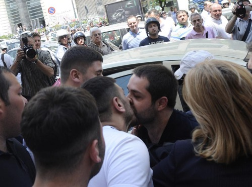 Suspected Mafia member Daniele D'Agnese, right, kissed a friend as he was escorted to jail Wednesday in Naples, Italy. Some analysts believe the kiss could be a code, possibly meaning to 'keep silent.' GETTY IMAGES/ AFP/ Controluce
