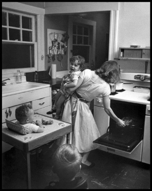 Elliott Erwitt, New Rochelle, NY, 1955 A nice domestic scene with his wife and kids. Erwitt's son Misha interviewed him about this photo:   Misha: You took a photograph in 1955 of our mother cooking dinner, her back to the camera. She has Ellen, who's crying, in one arm and she's reaching into the oven with the other. I'm sitting behind them in a high chair and there's another kid standing, watching. What's the back story to that photo? Also, you were traveling all over the world, on the road constantly. What was it like to come home from an exotic locale to a house full of screaming kids? Elliott: There is no story behind that photo, just a moment of the normal chaos of a family with numerous children. I loved coming back home to screaming children.   I don't know about you, but it boggles my mind to see that women actually (as opposed to being in ads) wore heels and dresses just to cook and carry around screaming toddlers back in the day.