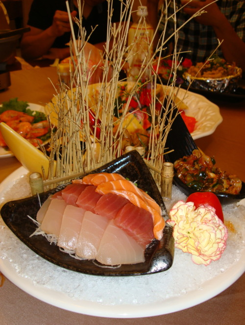 Vacationing in Taiwan Food Frenzy Epi 12. Sushi Platter. Sashimi over a bed a shredded daikon radish with an escargot salad side dish and a sweetened black bean side dish.