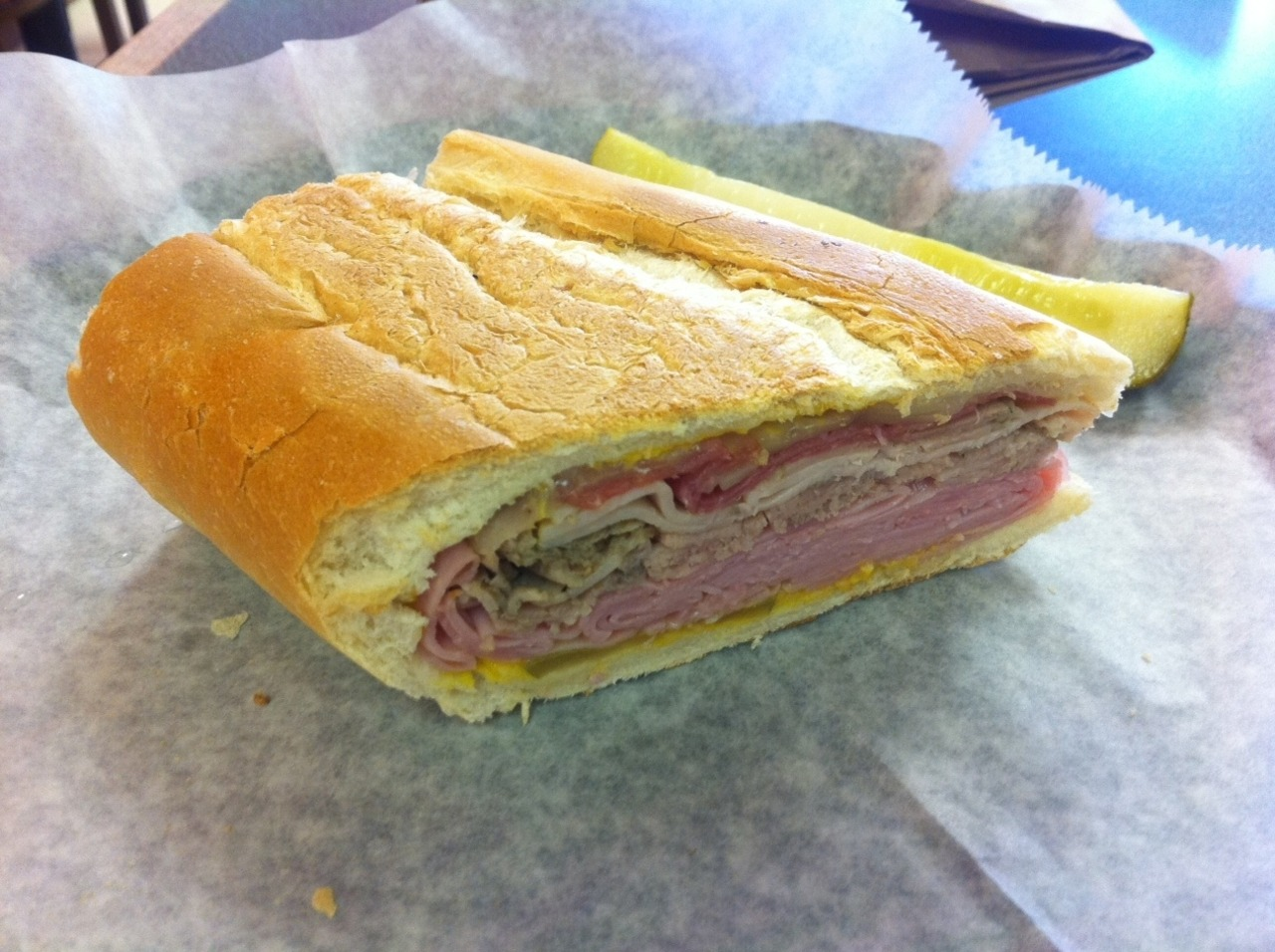 Cuban Sandwiches We Have Known Roving sandwich reporter Todd Sturtz checks in again, this time from Crazy Ray's on Kennedy Boulevard in Tampa:  Crazy Ray's Deli opened in October 2010 in the space formerly occupied by Moxie's, and offers a plethora of sandwiches. And I mean a plethora. At least 30 or more (including some breakfast sandwiches), with a variety of sizes and ingredients. I was driving by on my way to get a haircut and Ray's colorful orange signs caught my attention, so I stopped to investigate.The decor was bright and colorful, not necessarily tasteful - unless of course you're orange and yellow is your thing, in which case you'll LOVE it. Although labeled a deli, I don't recall seeing any deli counter inside, more like a typical sandwich shop with a big menu on the wall and a soda fountain off to the side with napkins and condiments keeping it company.Many of Ray's sandwiches are on Cuban bread, which I was told is sourced daily from the Casino Bakery (Ybor City). Not surprisingly, the Cuban sandwich I ordered ($6.49) also came on said bread, and per usual, I requested it well pressed, sans lettuce/tomato/mayo. As you can see from the picture, the sandwich had a generous amount of meat on it, the most discernable of which was the thin-sliced ham when biting through the crunchy shell into the soft layers of bread, meat, and cheese. When putting this Cuban up against my recent visits to Wright's & Floridian, I must concede it would scarcely be a contender, even though it was the most meatily adorned of the three. The ham really stole the show, in a briny sort of way (not bad mind you, this would be quite enjoyable to one with a penchant for ham sandwiches and/or salt), while most everything else in the sandwich took a back seat. The salami was nowhere near as prevalent as it was in Floridian's (and I really would have loved it if the Ray's bread had a tiny bit of butter on it like Floridan), and the roast pork was in attendance, but hardly with the presence it had in Wright's.I'd go to Ray's again, but to explore the rest of the menu, not for the Cuban. Especially not with the Floridian a literal stone throw away