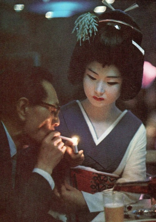 crazy70s:  Geisha presents a light to a diner in a Tokyo restaurant, 1969