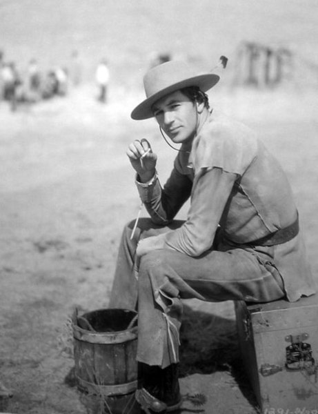 Gary Cooper takes a cigarette break on the set of Moving Caravans - (1931)