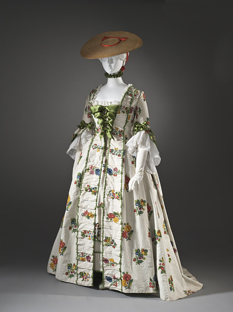 The modesty required by mid-18th century fashion did not allow for much skin to be exposed no matter how hot the weather. To get around this, and assure women didn't drop like flies from heat stroke, summer gowns were made from cotton or linen, which was lighter and far more breathable than the heavy silk damasks usually used. This robe à la française, dating to circa 1760 and made of slightly earlier material, is made of a plain weave linen and embroidered with colorful flowers in wool. (Yes, the flowers are all embroidered, not printed!) The ensemble is completed with a flat straw hat known as a bergère which served as a sort of wearable parasol and allowed 18th century women to maintain their fashion-mandated pale complexion while keeping their hands free.