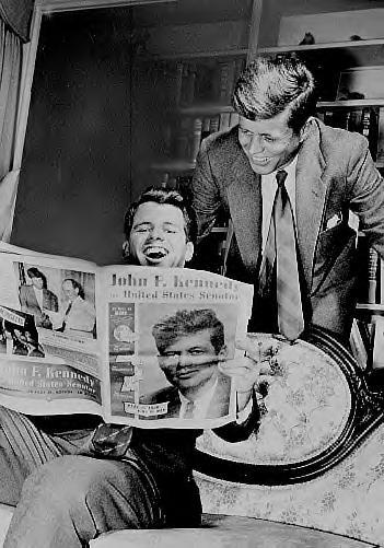 Bobby laughing at an article about JFK.   Sweetest brothers ever!
