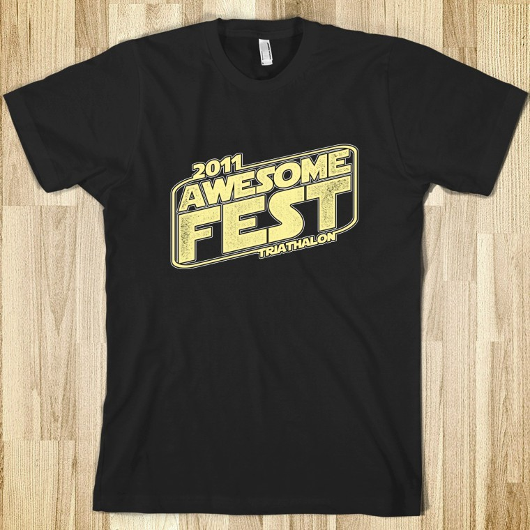 Official Awesomefest 2011 Tee This year, we are happy to be using Skreened to produce our tee-shirts. For those of you who aren't familiar with them, they allow you to produce and purchase one-off shirts for an affordable price. This way, we can have multiple designs available in a variety of cuts and colors. So feel free to buy your shirt today as we will not be selling them the day of the event. And make sure to keep checking back to the shop for additional Awesomefest shirt designs.