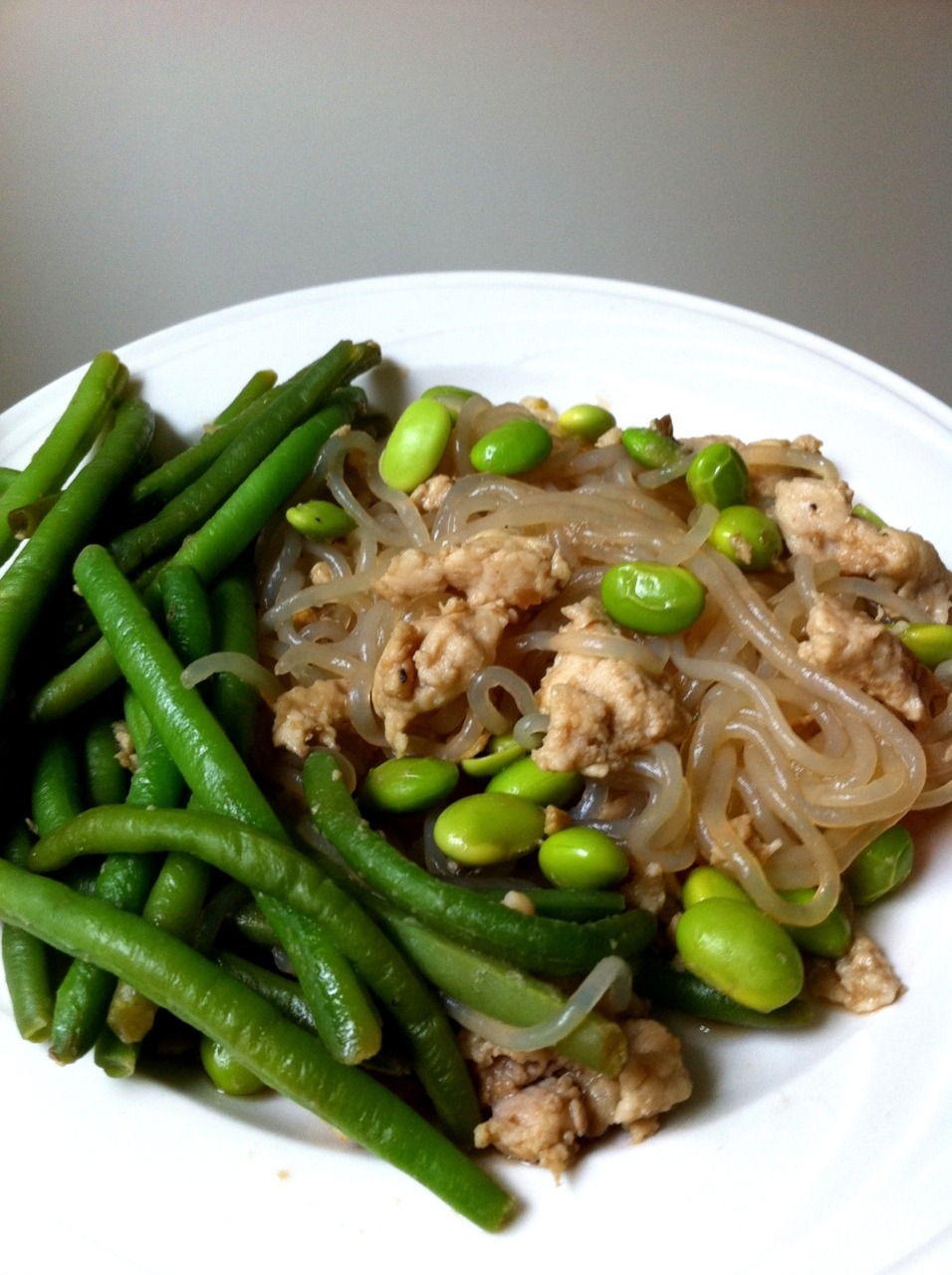Miracle Noodle Teriyaki Green Beans, Edamame, & Pork Dish Oh so yummy! This was SUPER FAST to make. I think it literally took like 5 minutes to throw this whole thing together. I spent more time taking pictures than cooking. I should win an award for fastest healthy chef ever. INGREDIENTS: *1 serving french cut green beans (Trader Joes) or you can use any green bean *1 serving edamame, shelled (Trader Joes) *3-4oz of ground meat (I used pork because I had that laying around) *1 TBS Teriyaki sauce or to taste *1 packet of Zero Calorie Shirataki Miracle Noodle DIRECTIONS: 1. Drain your Miracle Noodles into a sifter and run under warm water until fishy smell disappears. (Don't worry about the smell, it is nothing harmful!) Let sit and dry while cooking other ingredients. 2. Throw the frozen green beans and edamame into a big frying pan. Once halfway cooked through, throw in your ground meat. Push around for a little bit then add the terayaki sauce. 3. Once the meat is cooked through, dump Miracle Noodles on! Taste. Add soy sauce or more teriyaki to your preference.  So done! It tasted great. Most of the time, I don't plan my meals and just throw together whatever I have laying around. Edamame cooks beautifully and tastes very buttery. Tons of protein too in those little guys! The answer to a quick healthy meal is some nutritiously fresh ingredients and a happy sautee-er.  Enjoy! And if you have any questions on what Miracle Noodle is, read my post here on what it's made out of and why I love it. <3 Cassey
