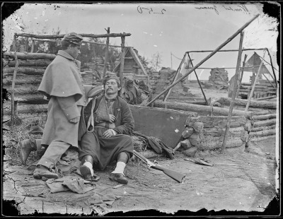 Photograph by Mathew Brady, injured soldier being tended to in an abandoned camp. US Civil War, 1865.