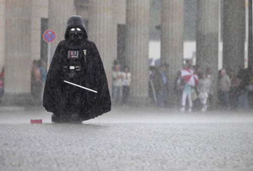 mabelmoments:  A soggy Darth Vader waits for tourists who want to be photographed with him in front of the Brandenburg Gate as storms drench Berlin. Times are hard for Darth  Despite the pathos of this photo, I find it quite heartening that in normal weather, Lord Vader gets enough business to warrant sticking it out through the bad times. Through Sith and thin, right?